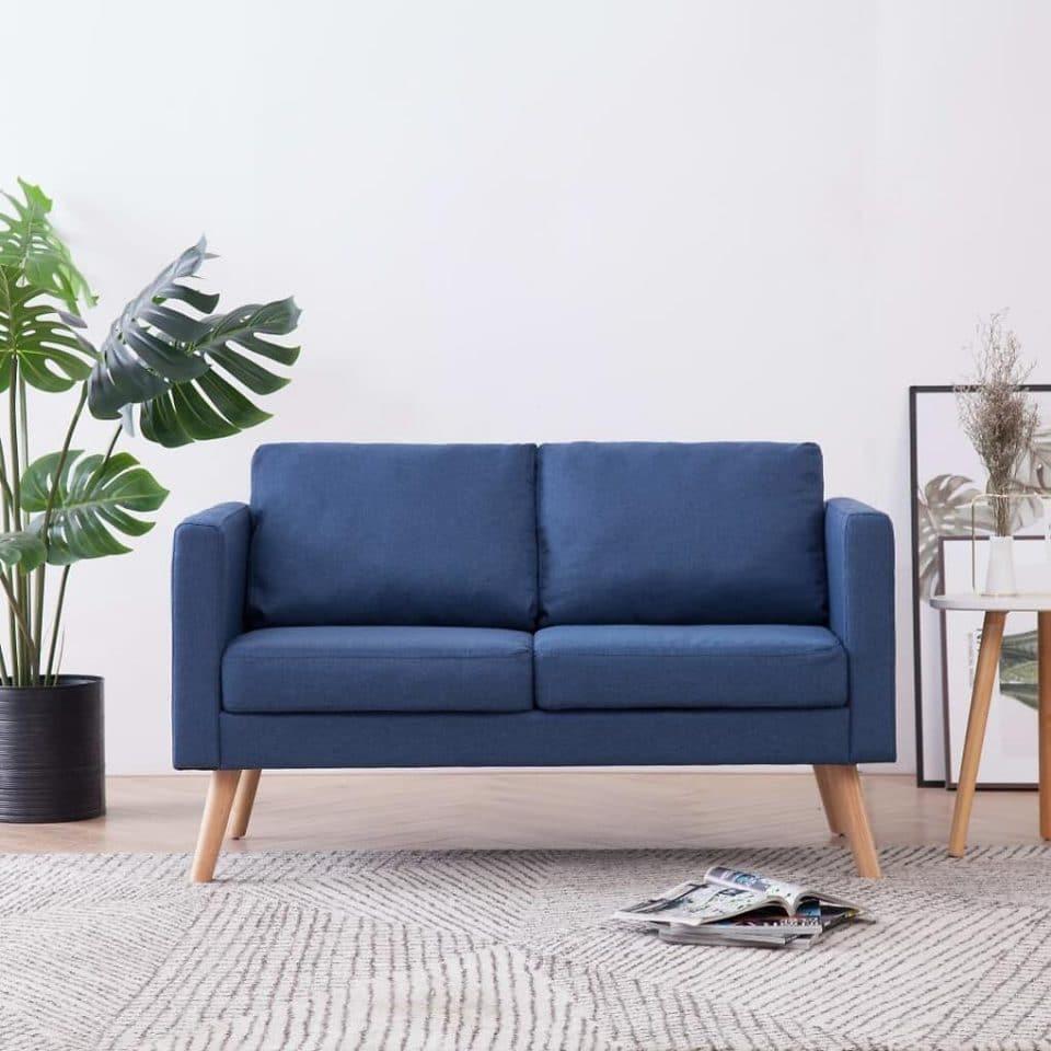 Modrá pohovka v obývacej izbe s látkovým poťahom v škandinávskom štýle