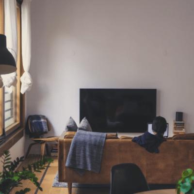 Plne vybavená obývacia izba s pohovkou uprostred miestnosti, lampou, televíziou a doplnky