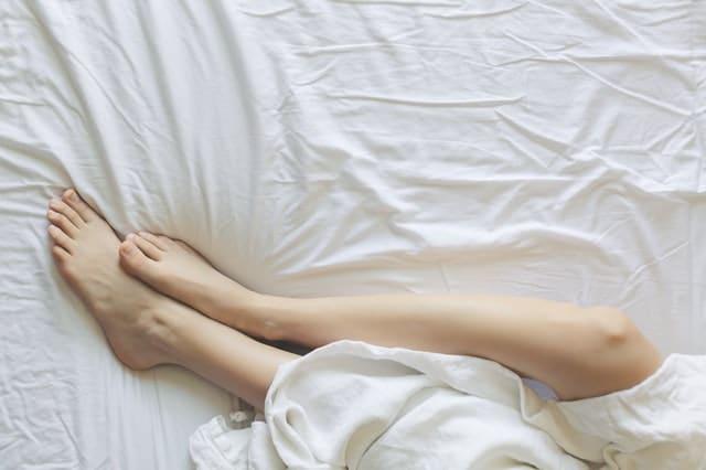 zenske-nohy-v-posteli-s-bielou-plachtou-a-obliečkou
