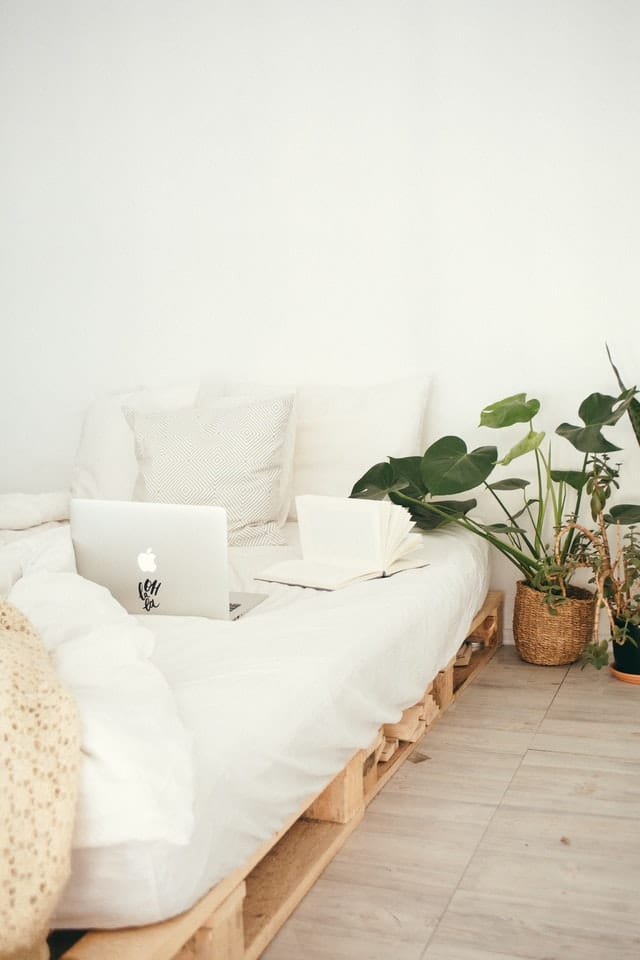hrubý-matrac-na-paletovej-posteli-biele-povlecenie-notebook-notes-kvety