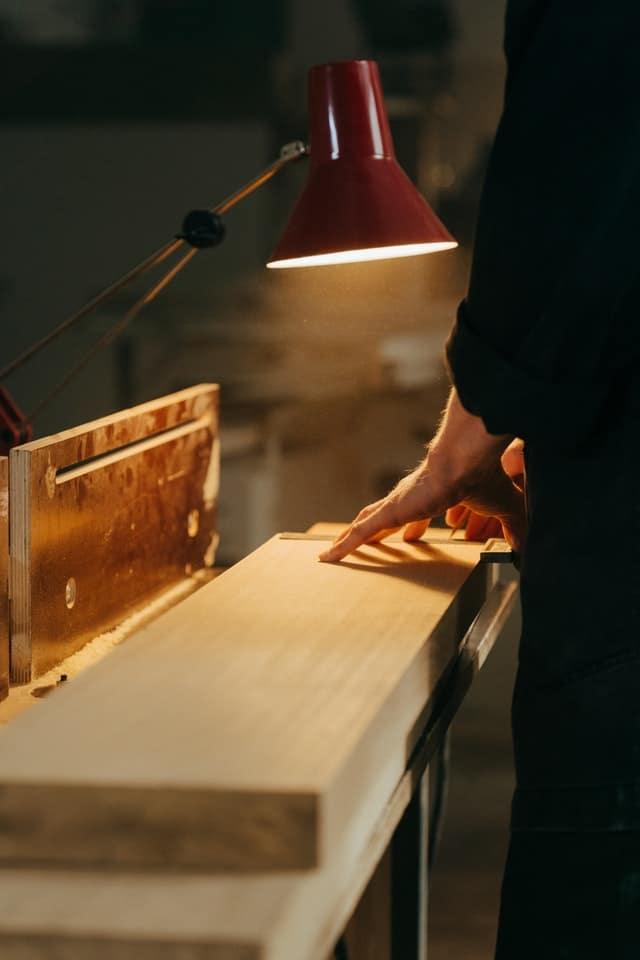 pracovny-stol-stolna-lampa-v-dielni-muzske-ruky-pracuju-s-drevom