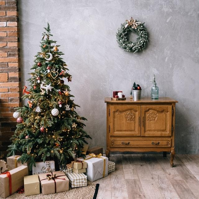 vianocne stromceky v interieri s darcekmi vedla drevenej komody
