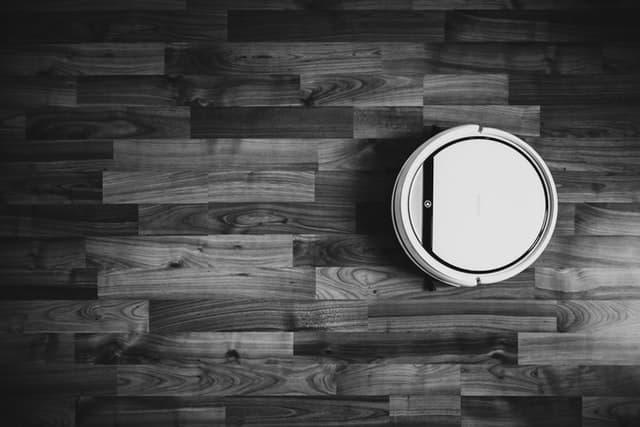 biely roboticky vysavac na tmavej drevenej podlahe