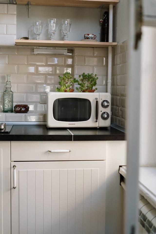 vintage mikrovlnna rura s bylinkami v kvetinach v rohu kuchynskej linky
